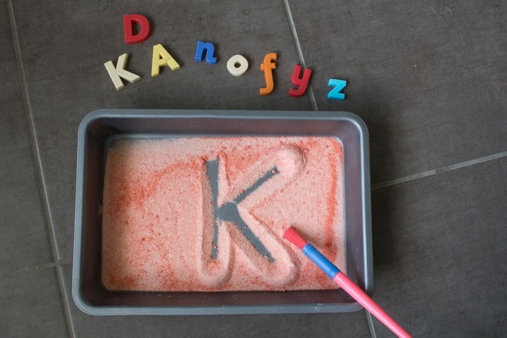 salt tray writing of the letter K a simple way to help children practice letter formation